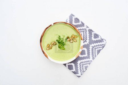 Photo for Top view of delicious creamy green vegetable soup with sprouts and pumpkin seeds on napkin isolated on white - Royalty Free Image