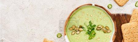 Photo pour Vue de dessus de soupe crémeuse verte savoureuse avec des craquelins sur planche à découper en bois, vue panoramique - image libre de droit