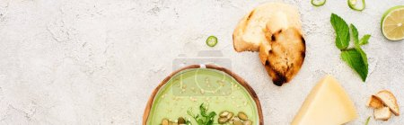 Photo for Panoramic shot of tasty green creamy soup with croutons and cheese on textured grey background - Royalty Free Image