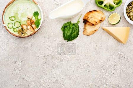 Photo pour Vue de dessus de soupe crémeuse verte savoureuse avec croûtons sur fond gris texturé avec espace de copie - image libre de droit