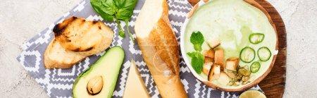 Foto de Foto panorámica de sopa cremosa vegetal verde en tabla de cortar madera con servilleta e ingredientes - Imagen libre de derechos