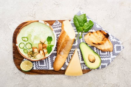 Photo for Top view of green vegetable creamy soup on wooden chopping board with napkin and ingredients - Royalty Free Image