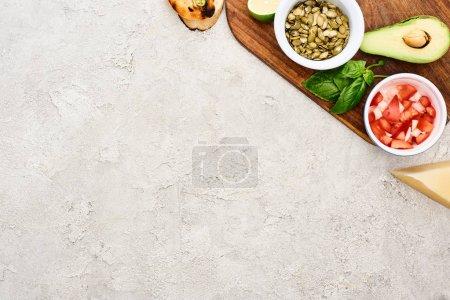Foto de Vista superior de semillas de calabaza, aguacate, menta y tomates en tabla de cortar madera - Imagen libre de derechos