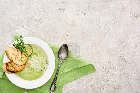 Photo for Top view of delicious creamy green vegetable soup with croutons served with spoon and green napkin - Royalty Free Image