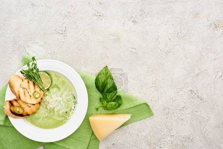 Photo for Top view of delicious creamy green vegetable soup with croutons served on napkin near spinach leaves and cheese - Royalty Free Image