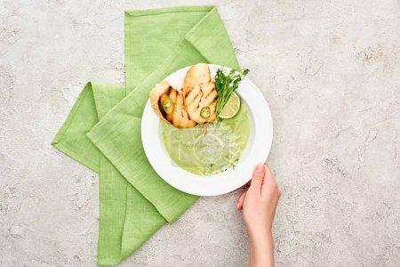 Photo pour Vue partielle de l'assiette de fixation de femme avec la soupe verte délicieuse de légumes avec des croûtons - image libre de droit