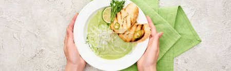 Photo for Cropped view of woman holding plate with delicious creamy green vegetable soup with croutons near green napkin, panoramic shot - Royalty Free Image