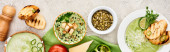 """Постер, картина, фотообои """"панорамный снимок вкусного сливочно-зеленого супа, подаваемого с овощами и гренками на зеленой салфетке"""""""