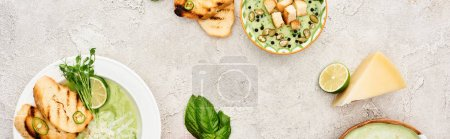 Photo for Panoramic shot of delicious creamy green vegetable soup served with greenery and croutons - Royalty Free Image