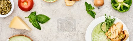 Photo for Panoramic shot of creamy green vegetable soup near fresh vegetables on textured surface - Royalty Free Image