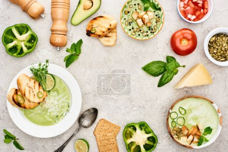 Photo for Top view of tasty creamy green vegetable soup in bowls near fresh vegetables on textured surface - Royalty Free Image