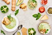 "Постер, картина, фотообои ""верхний вид вкусного сливочно-зеленого овощного супа в миски возле свежих овощей на текстурированную поверхность"""