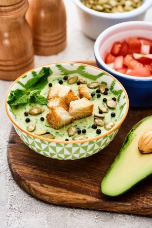 Photo for Bowl of delicious green vegetable creamy soup with croutons, black pepper and pumpkin seeds near avocado - Royalty Free Image