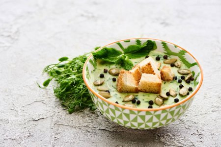 Photo for Bowl of delicious green vegetable creamy soup with croutons, black pepper and pumpkin seeds near green sprouts - Royalty Free Image