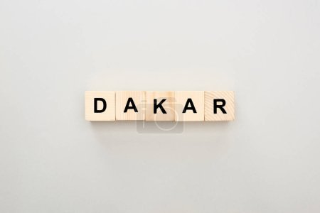 top view of wooden blocks with Dakar lettering on grey background