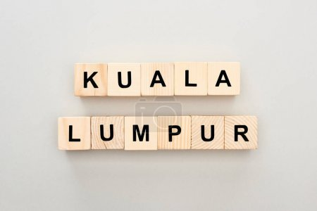 top view of wooden blocks with Kuala Lumpur lettering on grey background