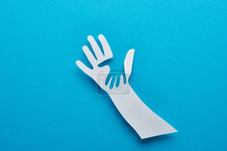 Photo for Top view of paper cut parent and child hands on blue background - Royalty Free Image