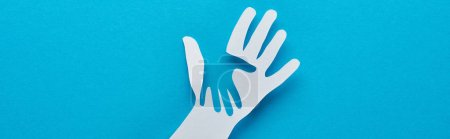 Photo for Top view of paper cut parent and child hands on blue background, panoramic shot - Royalty Free Image