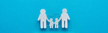 Photo pour Projectile panoramique de famille coupée de papier retenant des mains sur le fond bleu - image libre de droit