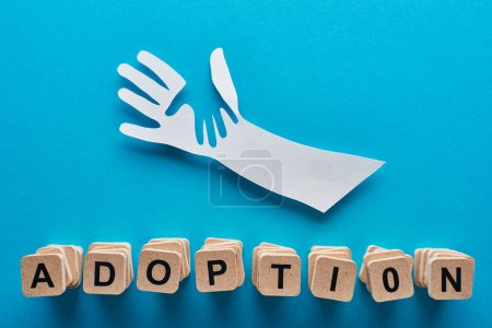 Photo for Top view of paper cut parent and child hands and adoption lettering on blue background - Royalty Free Image
