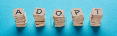 wooden blocks with adopt lettering on blue background, panoramic shot