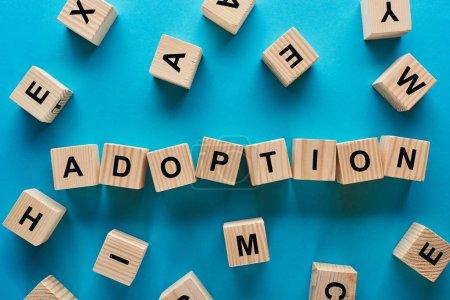 Photo pour Vue du haut du mot d'adoption fait de cubes en bois sur le fond bleu - image libre de droit