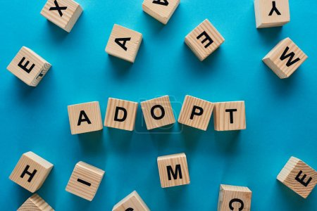 top view of adopt word made of wooden cubes on blue background