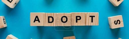 Photo pour Vue du haut de l'adoption mot fait de cubes en bois sur le fond bleu, tir panoramique - image libre de droit