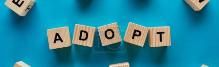 top view of adopt word made of wooden cubes on blue background, panoramic shot