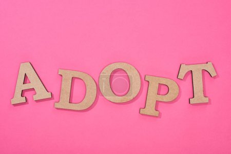 top view of cardboard word adopt on bright pink background