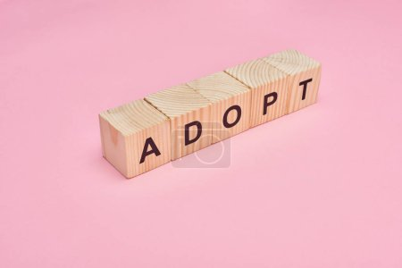 Photo for Wooden cubes with adopt lettering on pink background - Royalty Free Image