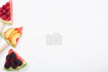 Photo pour Vue supérieure de la pastèque délicieuse sur des bâtonnets avec des baies saisonnières et de la pêche sur le fond blanc avec l'espace de copie - image libre de droit