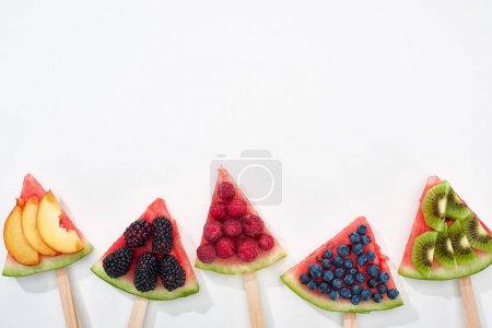Foto de Vista superior de sandía fresca en palos con bayas de temporada y frutas sobre fondo blanco con espacio de copia - Imagen libre de derechos