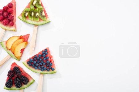 Photo pour Vue supérieure de pastèque savoureuse sur des bâtonnets avec des baies et des fruits saisonniers sur le fond blanc avec l'espace de copie - image libre de droit
