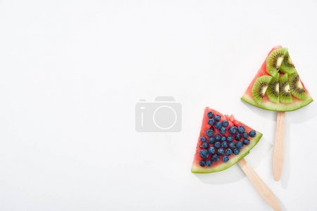 Photo for Top view of delicious watermelon on sticks with blueberries and kiwi on white background with copy space - Royalty Free Image