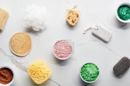 Foto de Vista superior de esponjas de baño de color, piedras pómez, sales de baño y máscara de arcilla en la superficie de mármol - Imagen libre de derechos