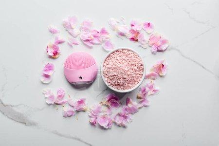 Foto de Vista superior del cepillo facial de limpieza de silicona y sales de baño en la superficie de mármol con pétalos rosados - Imagen libre de derechos