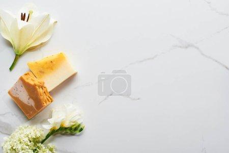Photo pour Vue supérieure des morceaux naturels de savon près des fleurs fraîches sur la surface de marbre - image libre de droit