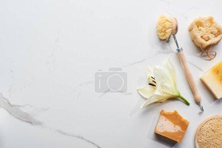 Photo pour Vue supérieure des morceaux naturels de savon, brosse de corps, loofah et éponge de visage près des fleurs fraîches sur la surface de marbre - image libre de droit