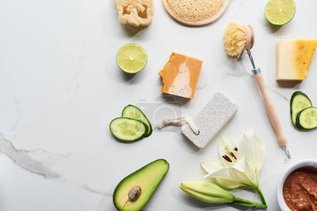 top view of natural soap pieces, body brush, loofah and pumice stone near fresh flower, lime, cucumber and avocado on marble surface