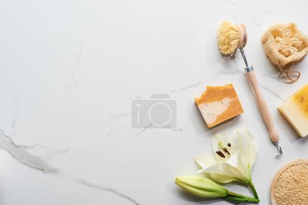 Photo pour Vue supérieure des morceaux naturels de savon, de brosse de corps et de loofah près de la fleur fraîche sur la surface de marbre - image libre de droit