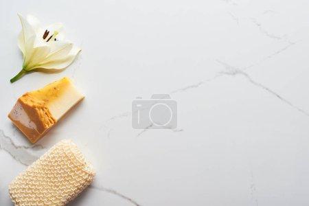 Photo pour Vue supérieure du savon normal près de l'éponge de bain et de la fleur fraîche sur la surface de marbre - image libre de droit