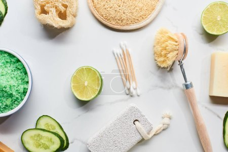 Photo pour Vue du dessus des sels verts de bain, brosse de corps, loofah, éponge de bain et pierre ponce près de la chaux fraîche et du concombre sur la surface de marbre - image libre de droit