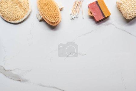 Photo pour Vue du haut du savon fait maison, éponges de bain, bâtonnets d'oreille et brosse de corps sur la surface de marbre - image libre de droit