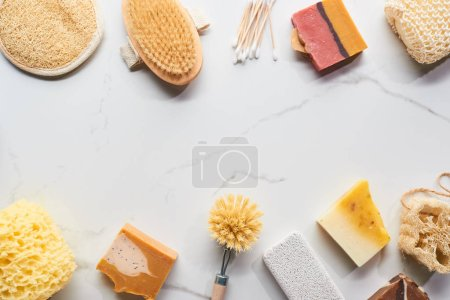 Photo for Top view of homemade soap, pumice stone, bath sponges, ear sticks and body brushes on marble surface - Royalty Free Image