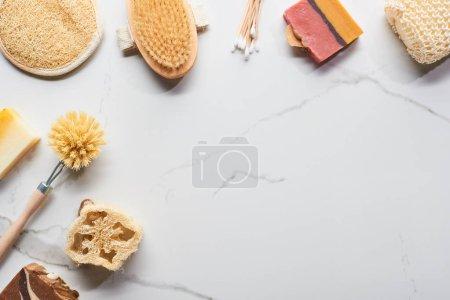 Photo pour Vue supérieure des bâtonnets d'oreille, des éponges de bain, du savon, du loofah et des brosses de corps sur la surface de marbre - image libre de droit