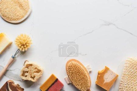 Photo pour Vue du haut du savon naturel fait maison, du loofah, des éponges de bain et des brosses de corps sur la surface de marbre avec l'espace de copie - image libre de droit