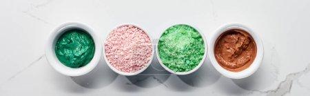 Photo pour Coup panoramique des tasses avec des produits de beauté de couleur sur la surface de marbre - image libre de droit