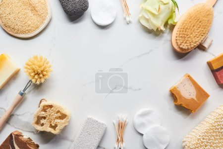 top view of homemade soap, bathroom accessories and flower on marble surface with copy space