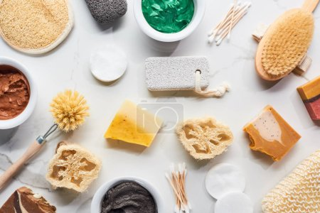 Photo for Top view of bath sponges, body brushes, hygiene supplies, soap and clay mask on marble surface - Royalty Free Image